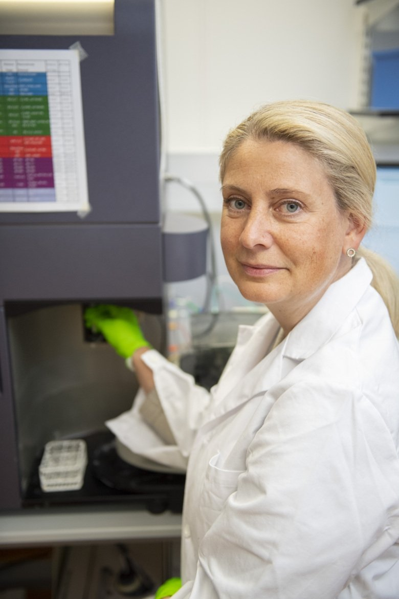 Portrait of Anna Smed Sörensen in the lab. She is blond, has a white lab coat and green gloves.