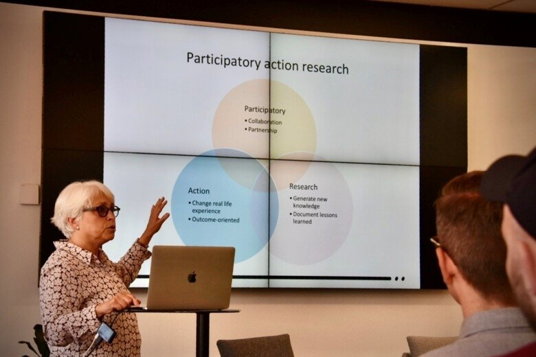 "Carol Tishelman presenting her research at the RMIT Health Transformation Lab, presenting a slide entitled ""Participatory Action Research"""