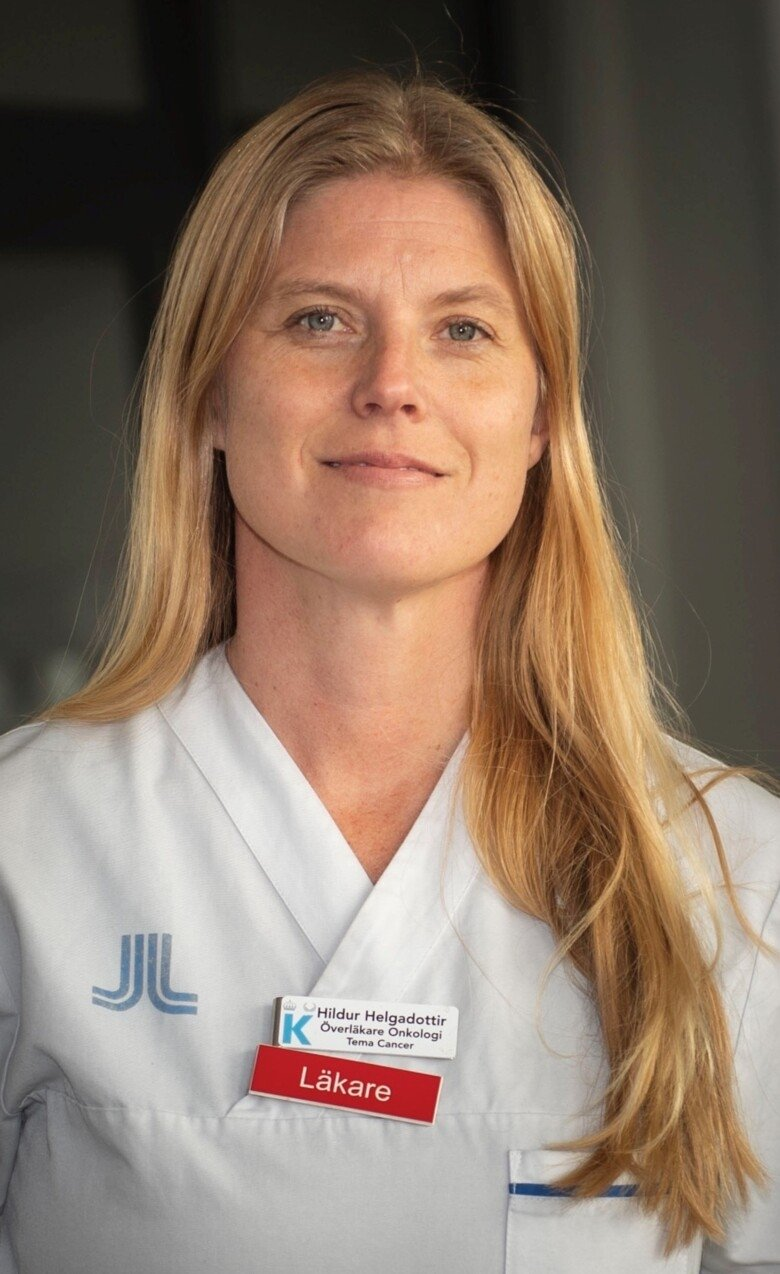 Portrait of Dr Hildur Helgadottir. She has long blond hair and is dressed in white scrubs.