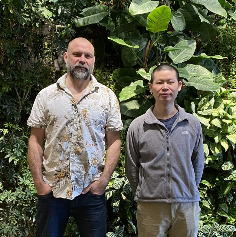 Two men standing infront of a wall of green plants.