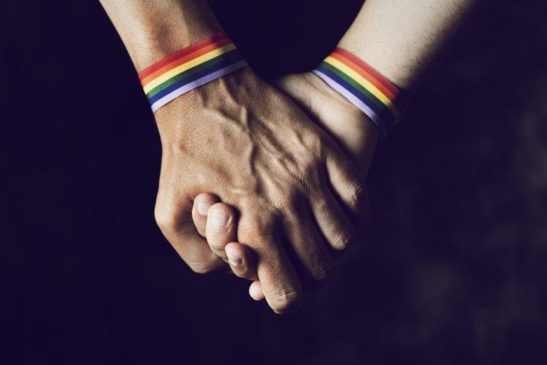 Men holding hands with pride bracelets