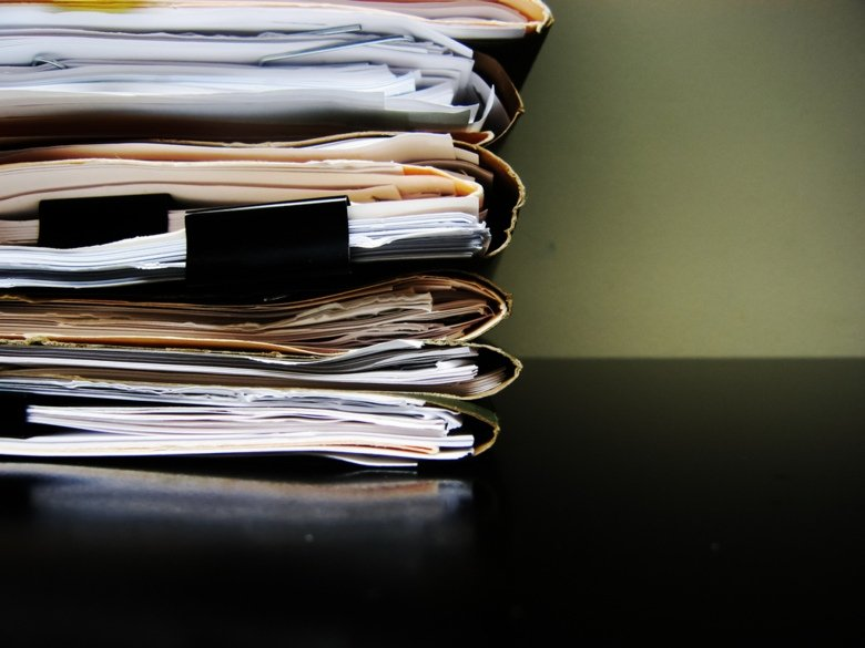 Stack of papers in folders on a table.
