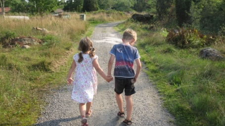 Two children walking away along a path