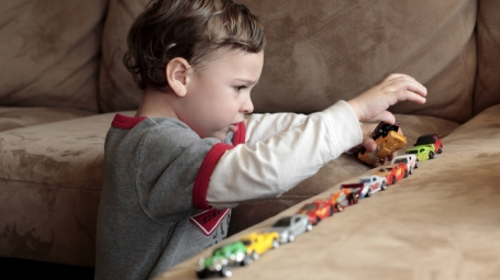 Young boy with autism playing with cars