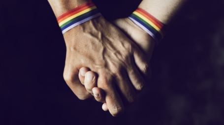 Men holding hands with pride bracelets