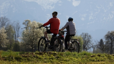 Two elderly people cycling in nature, they are both wearing helmets.