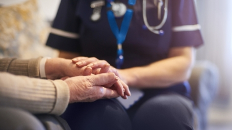 Photo of nurse holding elderly person's hands.