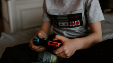 Boy holding video game controller, sitting on bed.