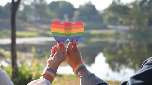 Homosexual couple holding up two rainbow-coloured hearts