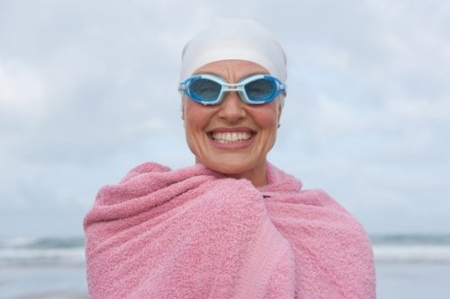 Smiling woman with bath towel coming from the sea.