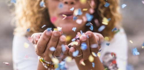 Photo of woman blowing confetti.