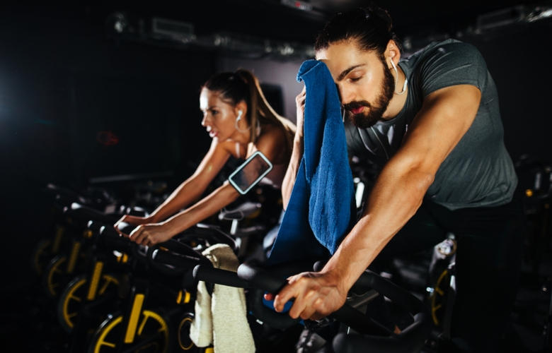 Photo of man and woman on exercise bikes.