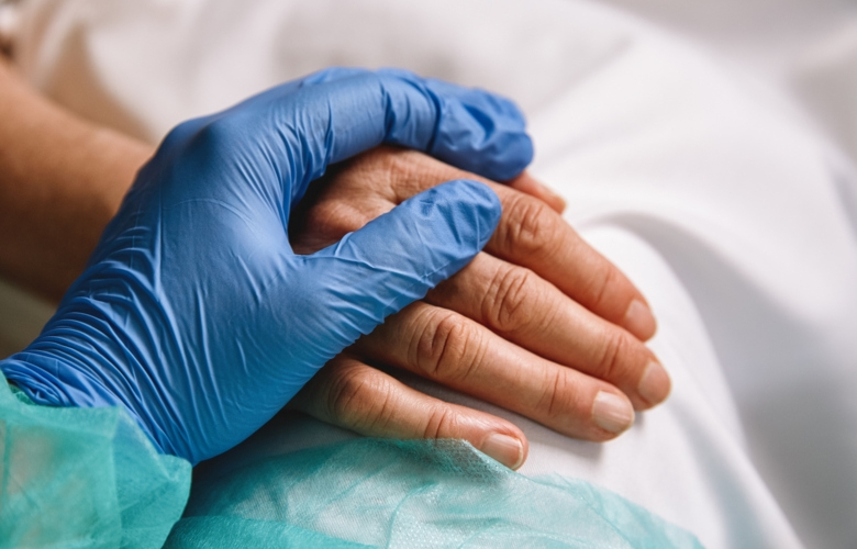 Medical staff in protective glove holds hand over patient's hand.