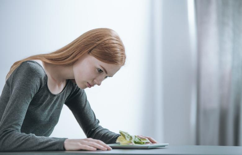 Photo of young woman weighing her food.